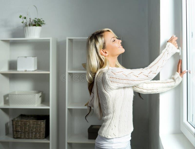 Jonge en mooie blonde vrouw die het venster openen stock foto's