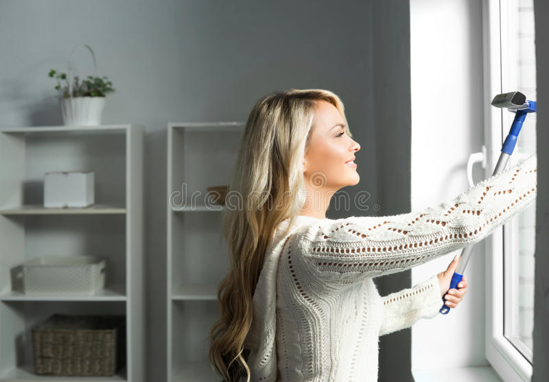 Jonge en mooie blonde vrouw die het venster schoonmaken stock fotografie