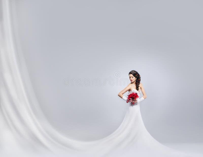 Jonge en mooie bruid die zich met een bloemboeket bevinden stock afbeelding