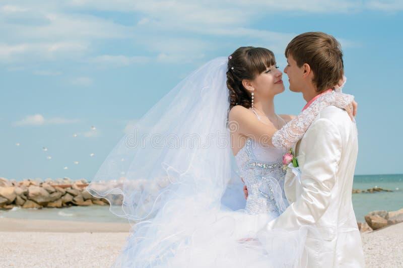 Jonge en mooie bruid en bruidegom op het strand stock fotografie