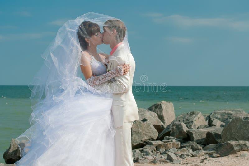 Jonge en mooie bruid en bruidegom op het strand royalty-vrije stock afbeelding