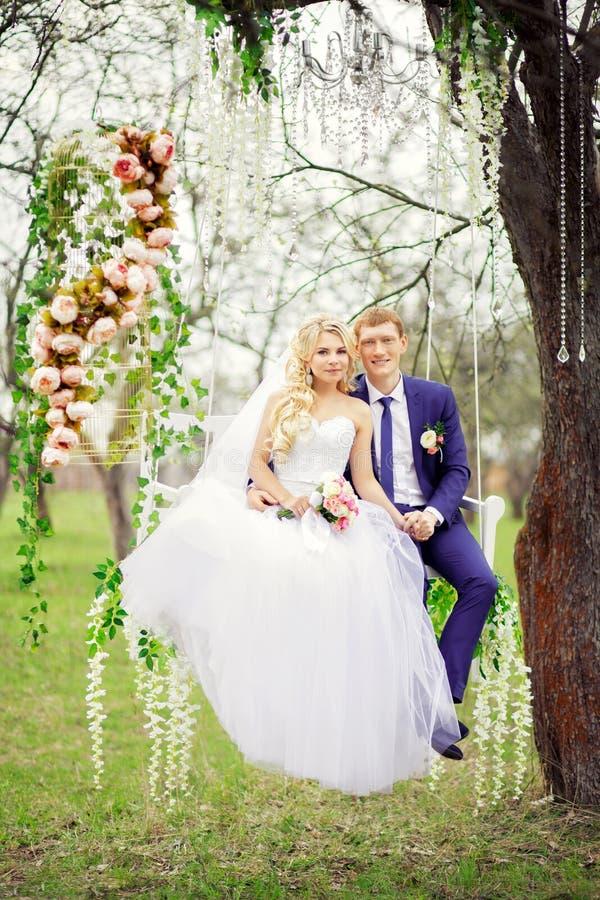 Jonge en mooie bruid en bruidegomzitting op een witte schommeling binnen stock foto