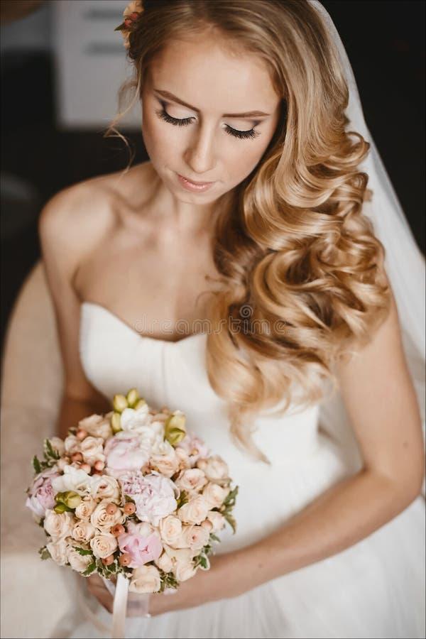 Jonge en mooie bruid, sensueel blond modelmeisje met zachte make-up en met huwelijkskapsel in de witte kleding royalty-vrije stock foto's