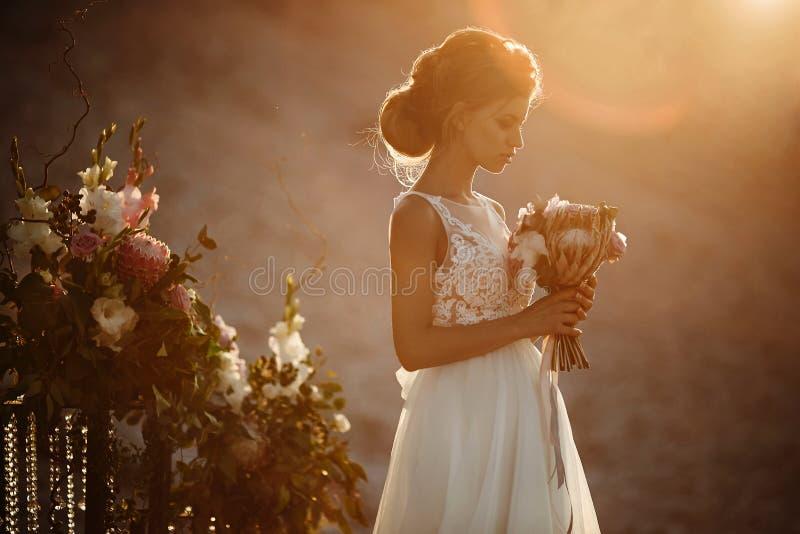 Jonge en mooie donkerbruine modelvrouw met de modellering van kapsel in modieuze witte kantkleding met boeket van exotisch stock fotografie