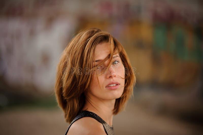 Jonge en mooie roodharigevrouw op de vage achtergrond van graffiti stock fotografie