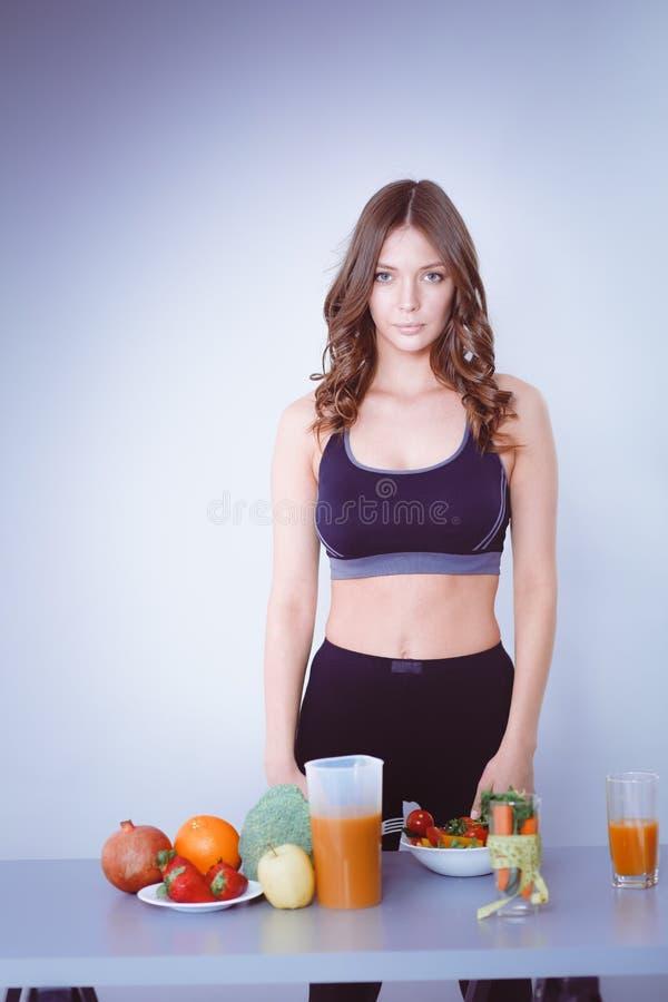 Download Jonge En Mooie Vrouw Die Zich Dichtbij Bureau Met Groenten Bevinden Stock Foto - Afbeelding bestaande uit dieet, gezondheid: 107705834