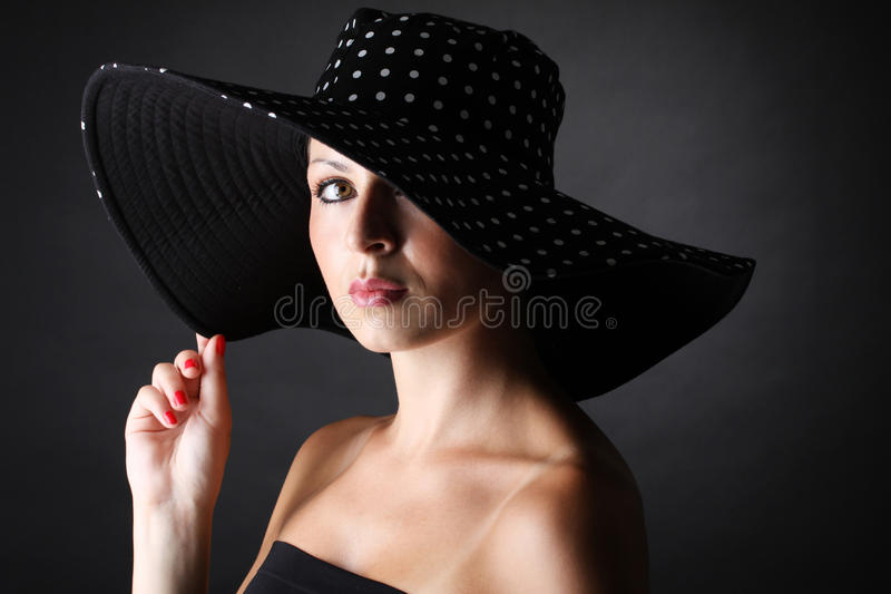 Jonge en mooie vrouw met hoed op zwarte achtergrond royalty-vrije stock fotografie
