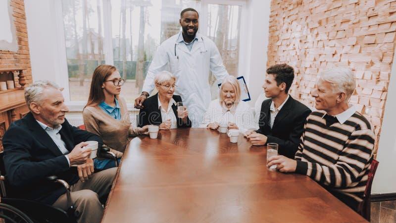 Jonge en Oude Mensen Sit Together Verpleeghuis stock foto's