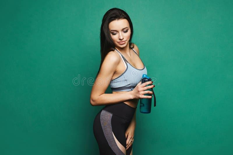 Jonge en sexy donkerbruine vrouw, fitness model met heldere samenstelling en perfect lichaam in sportuitrusting, strakke beenkapp royalty-vrije stock fotografie