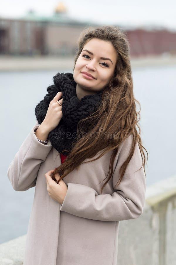Jonge en sexy vrouw in de laagherfst in openlucht Het meisje in een zwarte laag, een sjaal en een rood kleden zich tegen een grij royalty-vrije stock fotografie