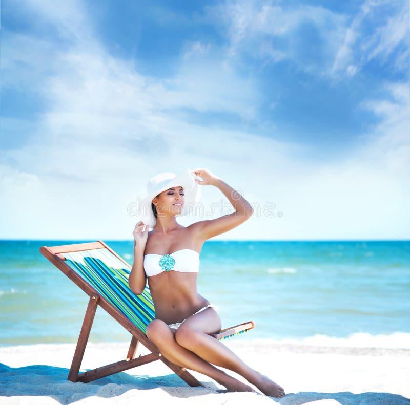Jonge en sexy vrouw die een hoed en een bikini op het strand dragen royalty-vrije stock afbeelding