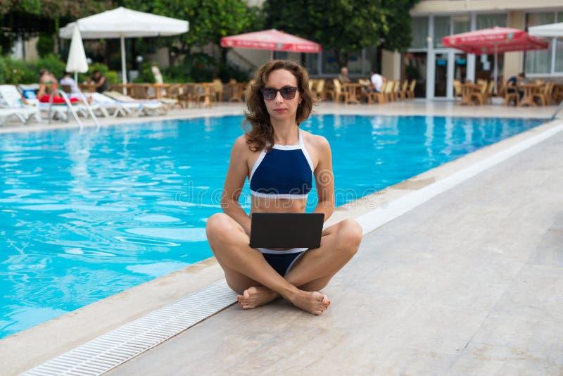 Jonge en slanke vrouw, in de lotusbloempositie die, die door de pool zitten en aan laptop werken Vrouwenwerkverslaafde die terwij stock foto