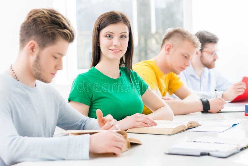 Jonge en slimme studenten die in een klaslokaal leren stock foto