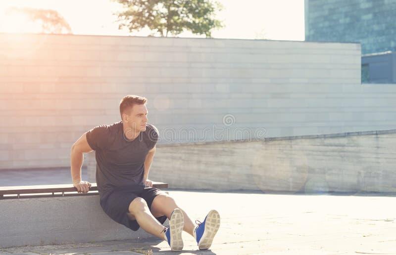 Jonge en sterke kerel opleiding openlucht in sportkleding Mens in een licht van zonsondergang Sport, gezondheid, fitness en stede stock afbeeldingen