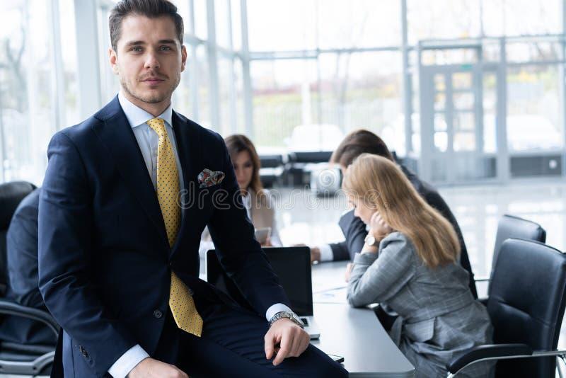 Jonge en zekere zakenman Knappe jonge mens in het formalwear glimlachen bij camera terwijl zijn collega's die werken aan royalty-vrije stock afbeeldingen