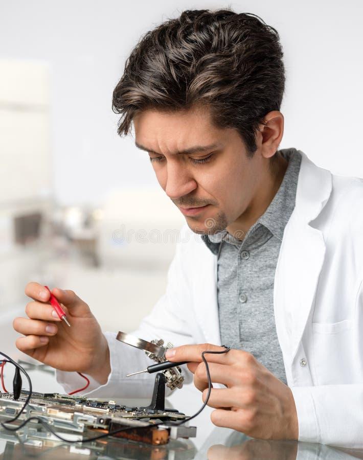 Jonge energieke mannelijke de reparaties elektronische equipme van technologie of van de ingenieur royalty-vrije stock foto's