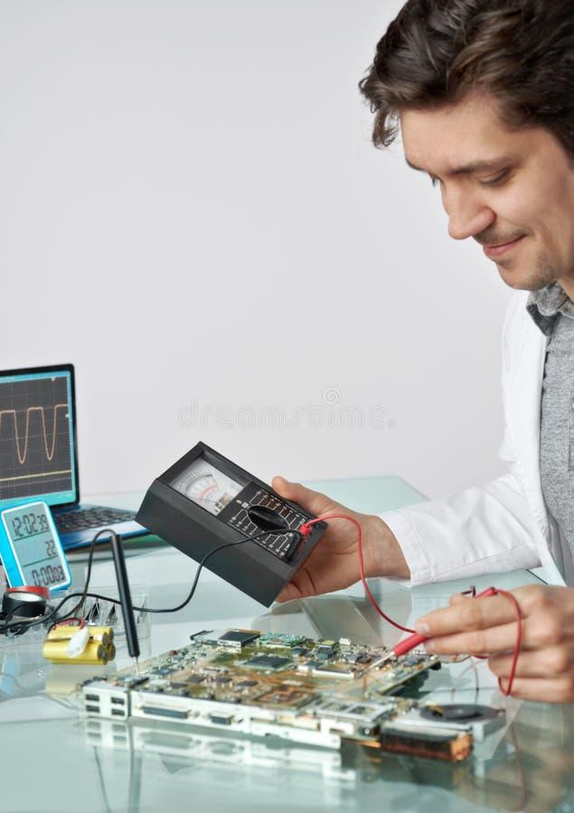 Jonge energieke mannelijke de reparaties elektronische equipme van technologie of van de ingenieur royalty-vrije stock fotografie