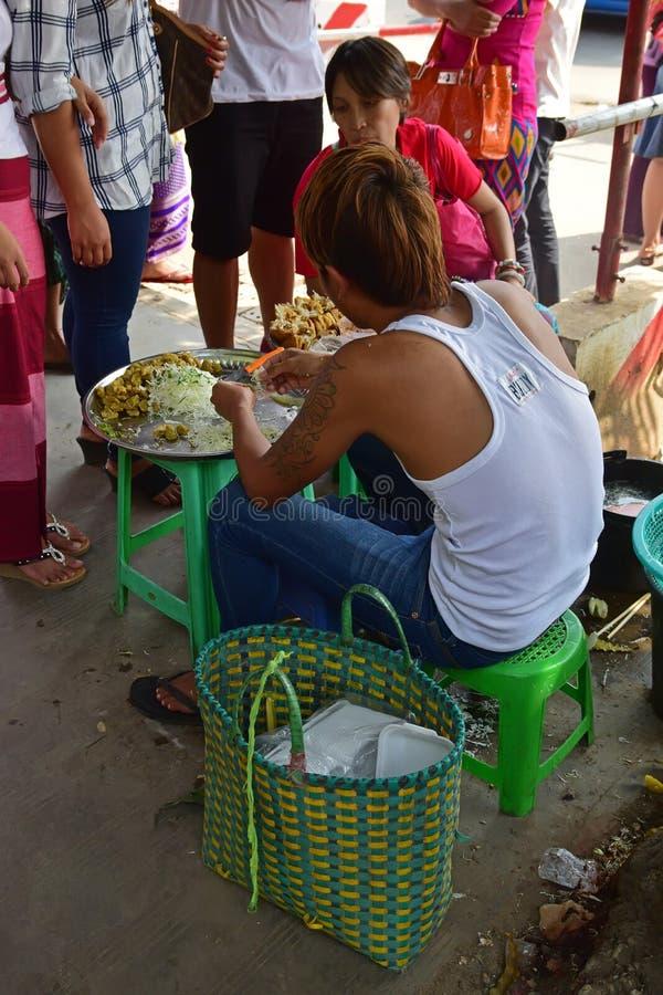 Jonge enige kant van de wegverkoper die & lokale favoriete snacks buiten Bogyoke-Markt voorbereiden verkopen in Yangon, Myanmar stock foto's