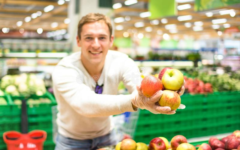 Jonge enige mens die fruit en groenten tonen bij het winkelen in gro royalty-vrije stock foto's
