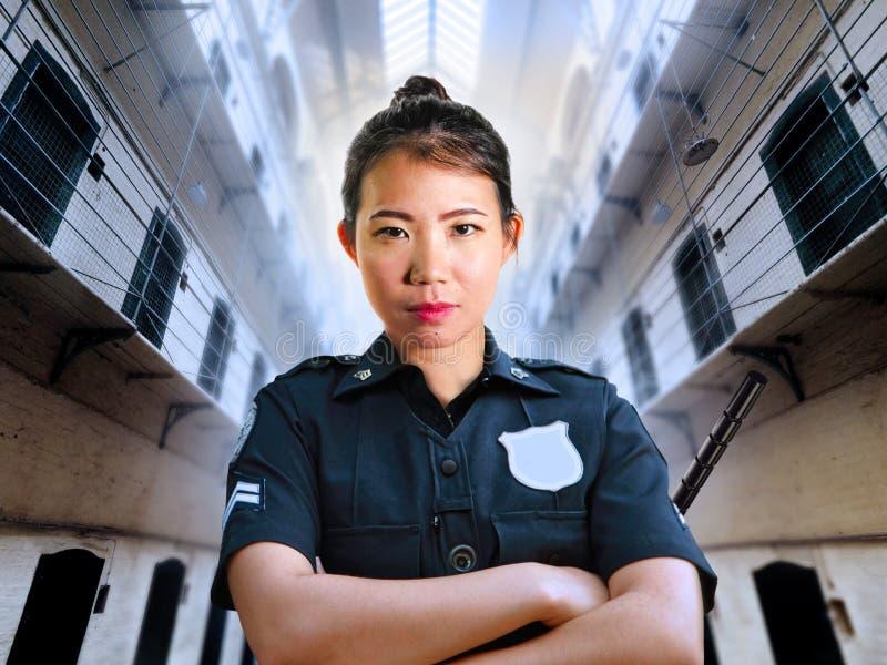 Jonge ernstige en aantrekkelijke Aziatische Chinese wachtvrouw die zich bij penitentiary van de Staat gevangeniszaal bevinden die stock foto's