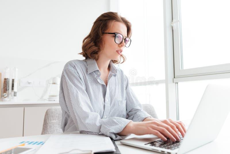 Jonge ernstige vrouw die in gestreept overhemd e-mail typen aan haar chef- wh stock afbeelding