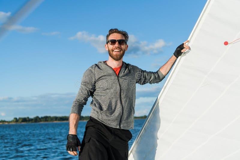 Jonge Europese mens die zich bij op zee rand van jacht bevinden die eruit zien Het reizen op oude boot met zeil Luxelevensstijl royalty-vrije stock afbeeldingen