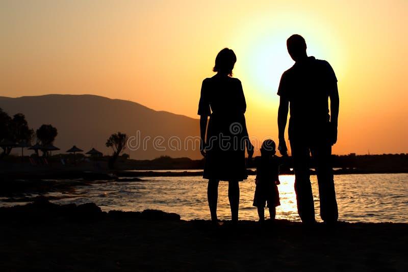 Jonge familie bij zonsondergang
