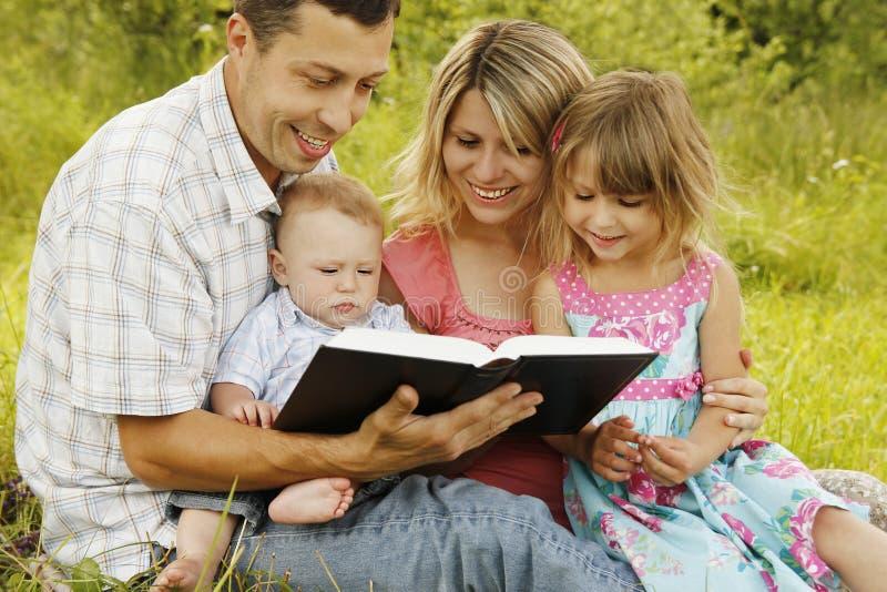 Jonge familie die de Bijbel in aard lezen royalty-vrije stock fotografie