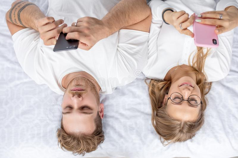 Jonge familie die hun mobiele telefoons met behulp van vóór de slaap stock foto's