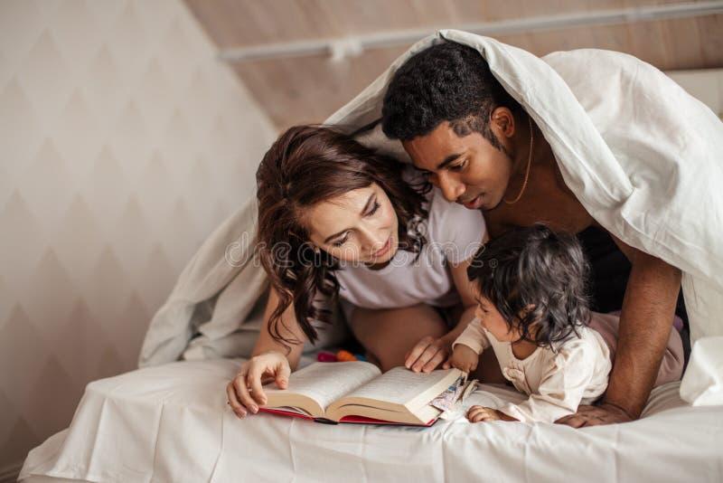 Jonge familie die interessant magisch verhaal lezen stock afbeeldingen
