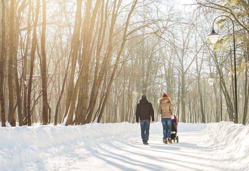 Jonge familie die met babywandelwagen lopen in park royalty-vrije stock fotografie