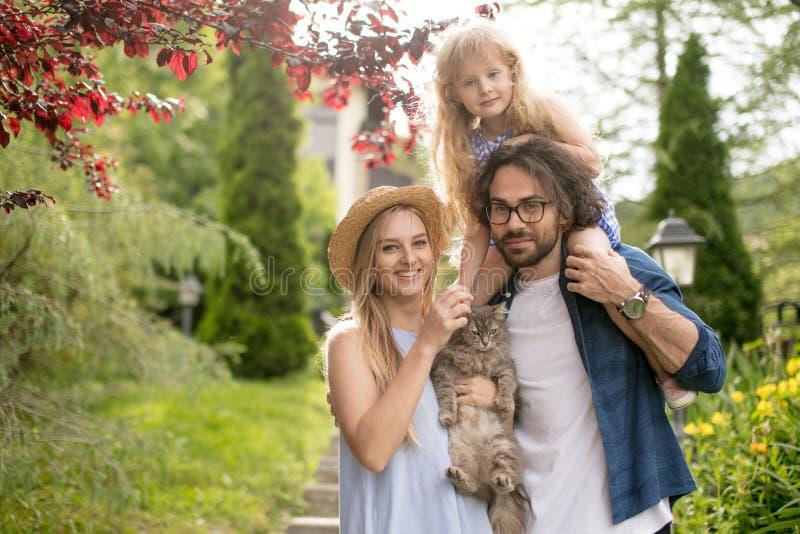 Jonge familie die met mand na picknick onderaan treden buiten in groen park lopen stock fotografie