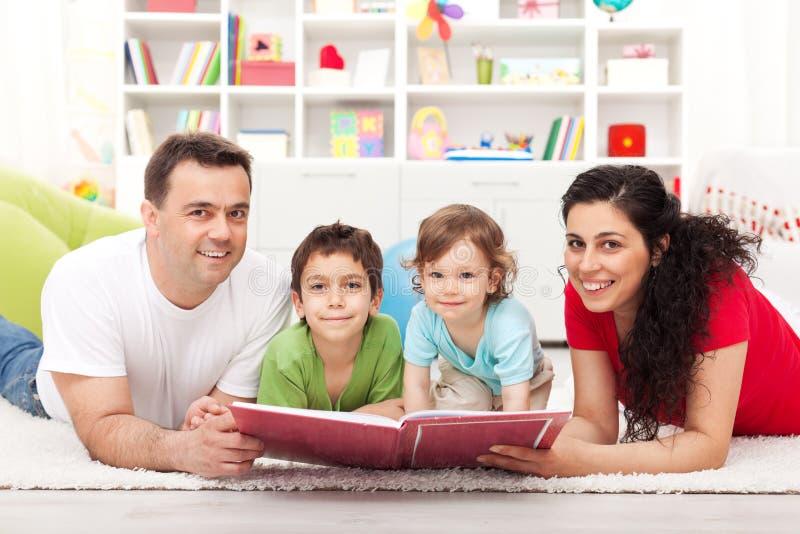 Jonge familie die met twee jonge geitjes een verhaalboek leest