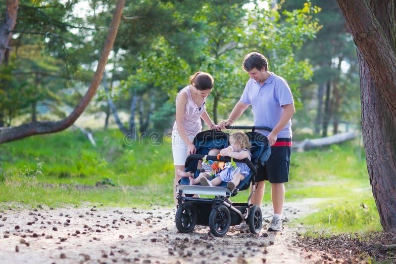 Jonge familie die met twee jonge geitjes in een wandelwagen wandelen stock afbeelding