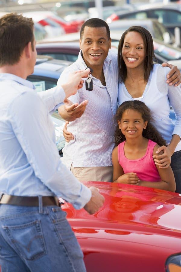 Jonge familie die nieuwe auto opneemt stock fotografie