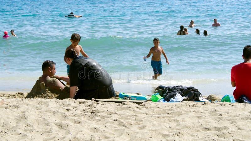 Jonge familie die op een zandig strand rusten royalty-vrije stock afbeeldingen