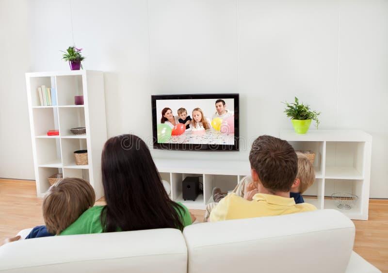 Jonge familie die op TV letten royalty-vrije stock foto
