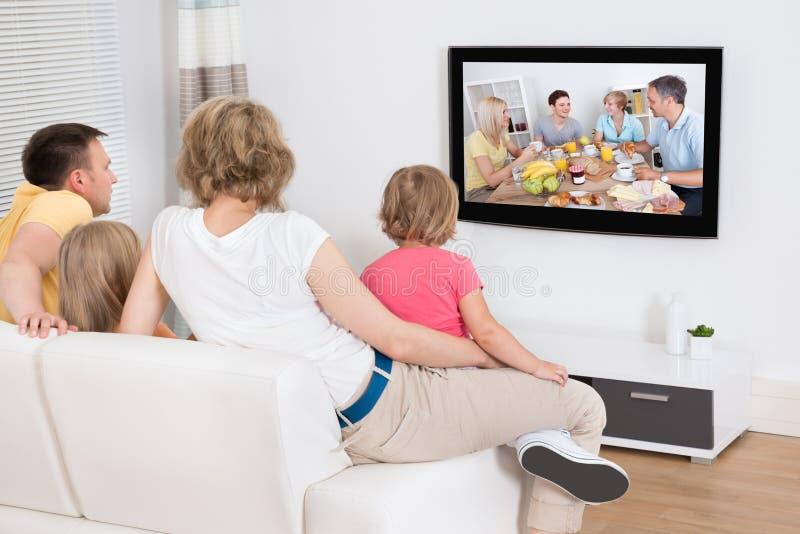 Jonge familie die op TV samen letten stock fotografie
