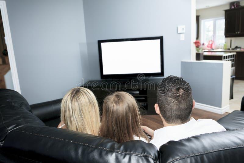 Jonge Familie die op TV samen thuis letten stock afbeeldingen