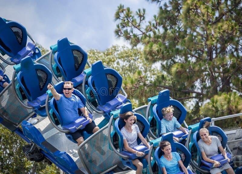 Jonge familie die pret hebben die een achtbaan berijden bij een themapark royalty-vrije stock foto