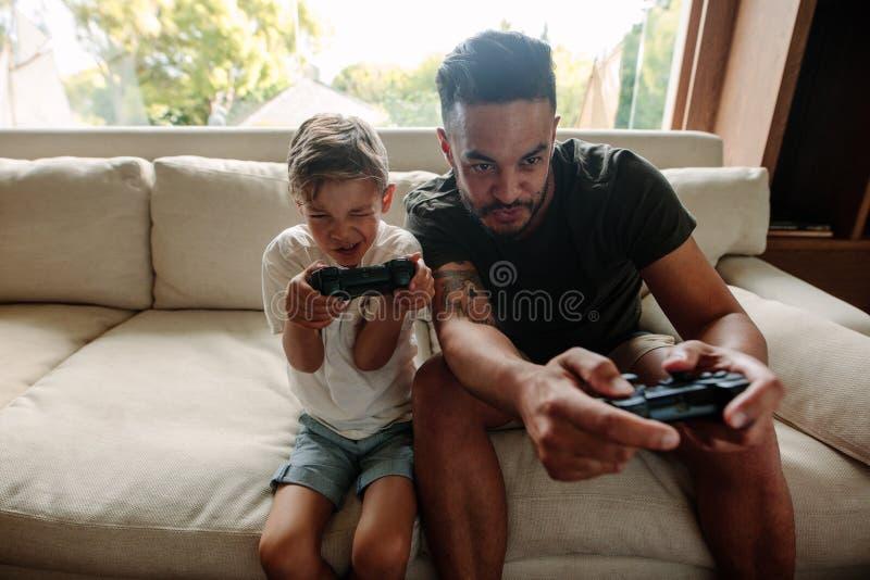 Jonge familie die pret het spelen videospelletjes hebben thuis royalty-vrije stock afbeelding