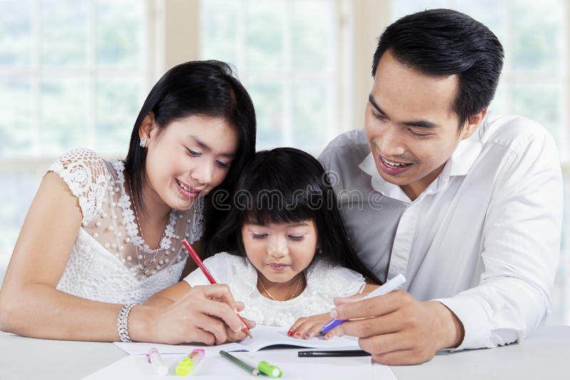 Jonge familie die schoolwork samen doen stock afbeelding