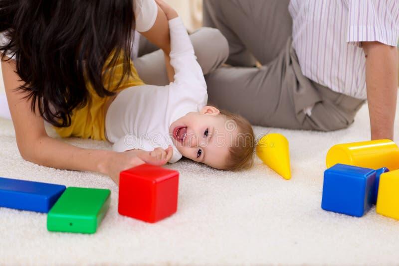Jonge familie die thuis met een baby spelen stock foto's