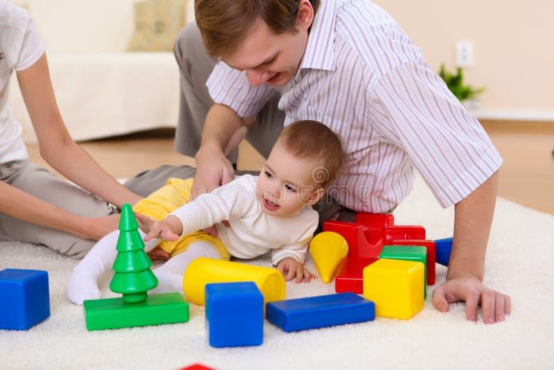 Jonge familie die thuis met een baby spelen stock afbeeldingen