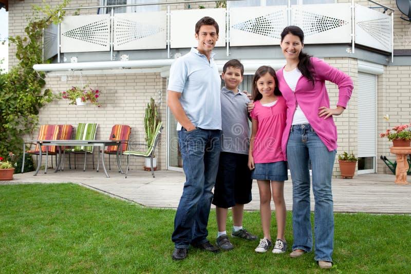 Jonge familie die zich voor hun huis bevindt