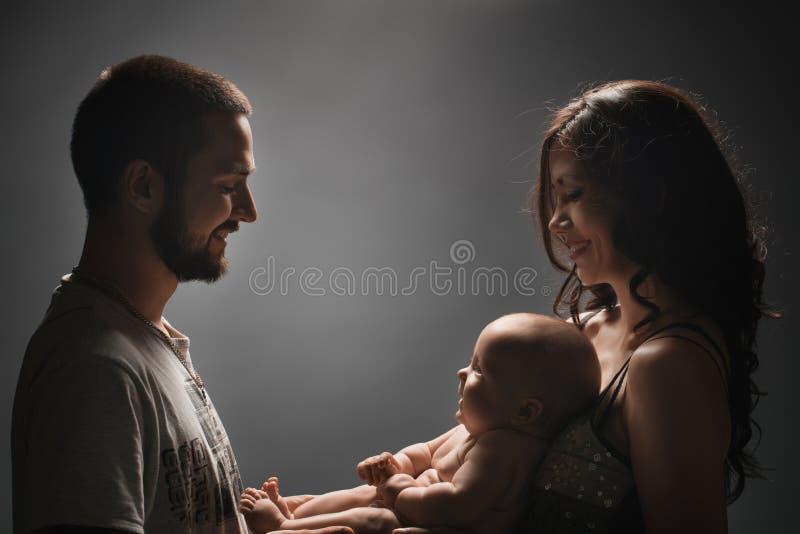Jonge familie en het pasgeboren schot van de babystudio stock afbeelding
