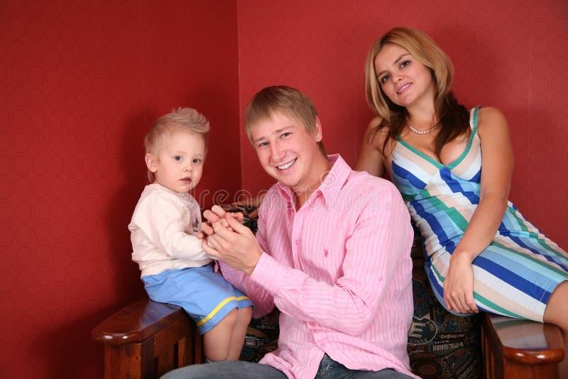 Jonge familie in leunstoel stock foto's