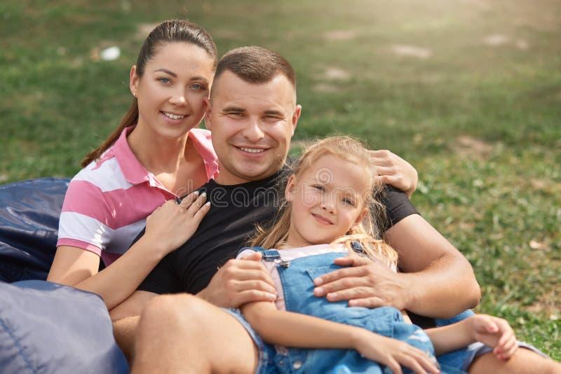 Jonge familie met aanbiddelijke doughter die pret in aard hebben, zittend op frameless stoel, bekijkend glimlachend camera, toeva stock foto's