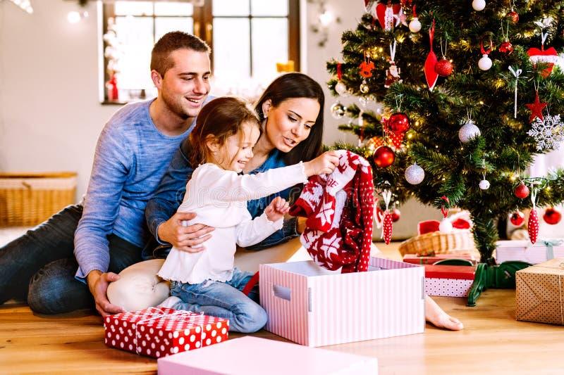 Jonge familie met dochter bij Kerstboom thuis stock foto's