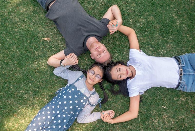 Jonge familie met dochter het leggen in het park op het groene gras en het bekijken de camera, hoogste mening royalty-vrije stock fotografie
